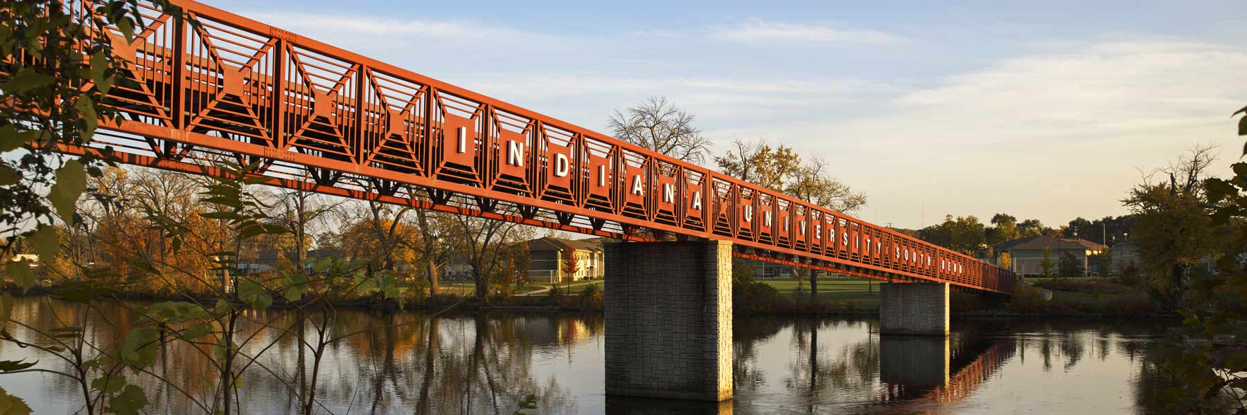 A red metal bridge over a river with Indiana University displayed in white letters.