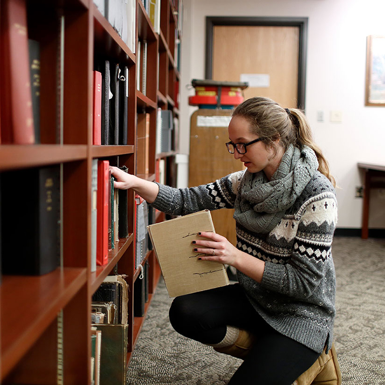 A woman in a gray sweater looks at books on a shelf.
