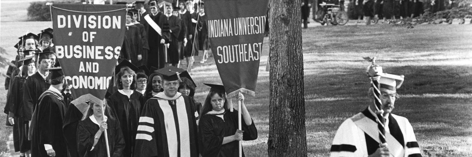 A line of graduates from IU Southeast walks to commencement