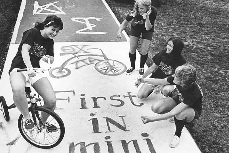 A black and white photo of a woman riding a tricycle as three other women stand by.