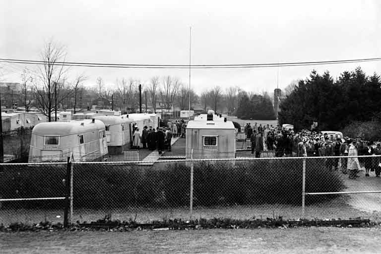 a field crowded with trailer homes and large groups of people standing around them