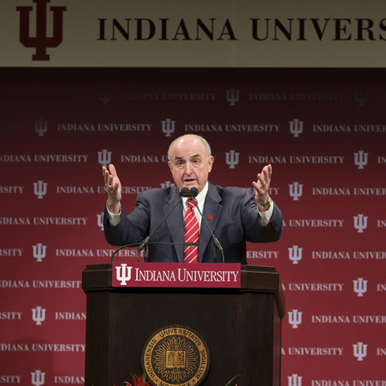 President Michael A. McRobbie stands with his hands in the air behind a podium.