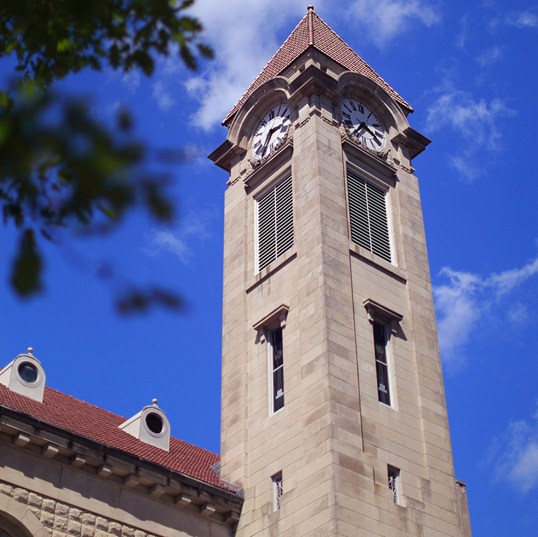 The limestone clock tower of the Student Building on the IU Bloomington campus against a blue sky.