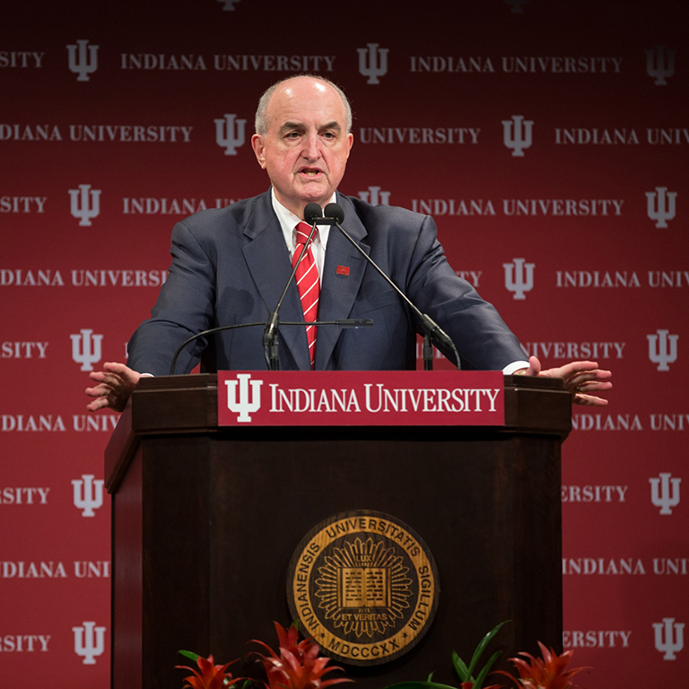 President Michael A. McRobbie standing at a podium in front of a red background with the words Indiana University.