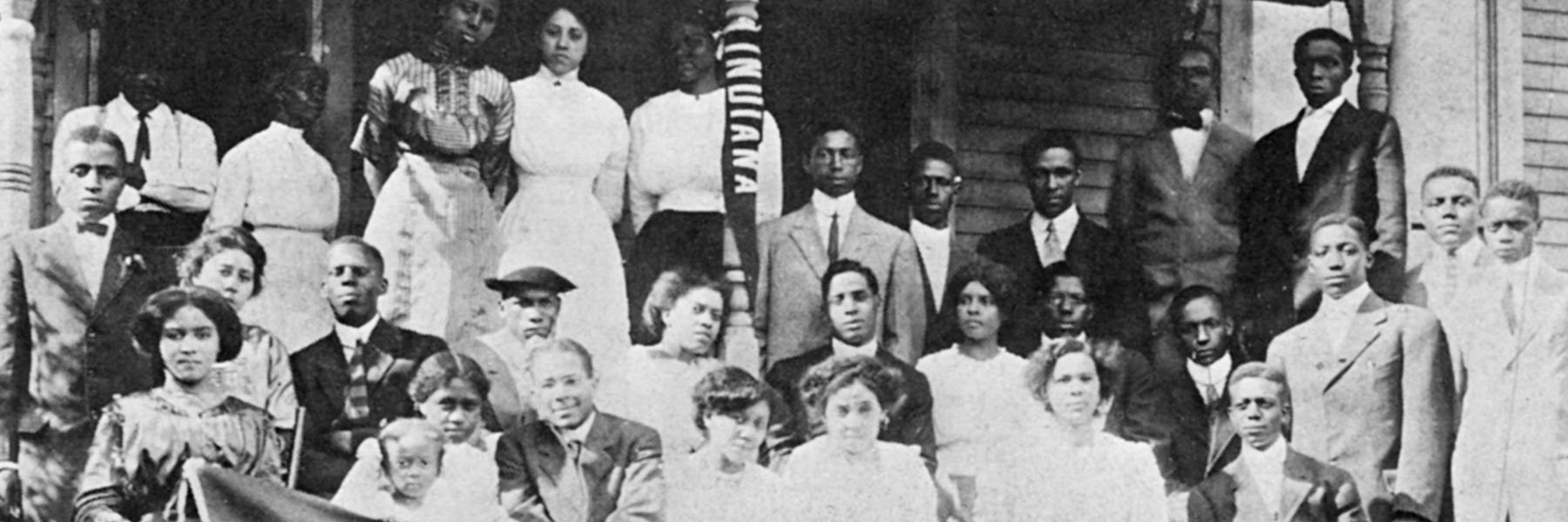 A black and white photo of a group of African American students standing with an Indiana University flag.