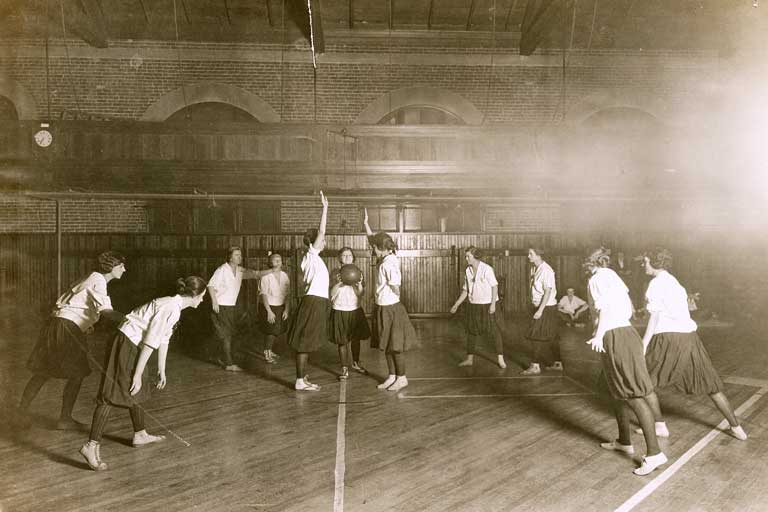A sepia-toned photo of a group of women in dark skirts and white shirts playing basketball.