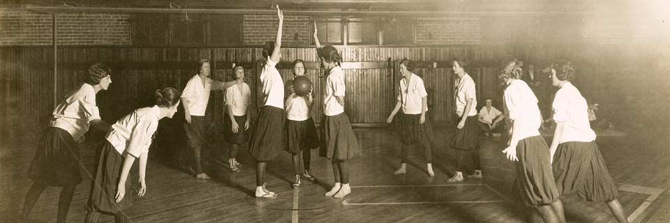 A sepia-toned photo of women in dark skirts and white shirts playing basketball.